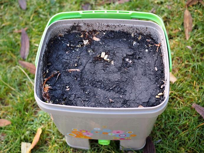Bokashi-Eimer mit Gemüseabfällen und Schicht aus Bio-Holzkohle